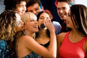 2644788-pretty-woman-sings-a-song-in-the-environment-of-her-friends-at-a-karaoke-party